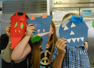 Students display the masks that they have created using critical thinking and problem-solving skills through art making.